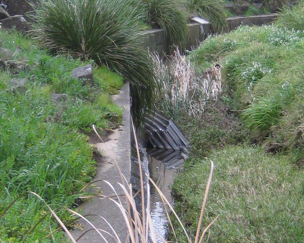 large piece of bent corrugated iron in the waterway