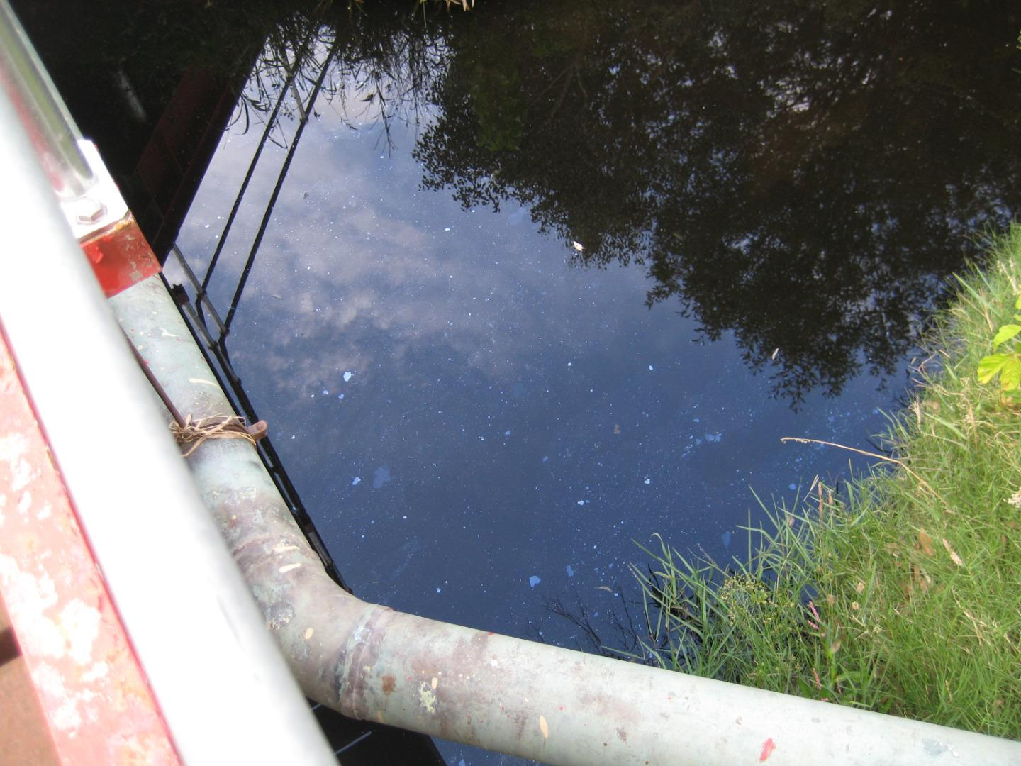 many patches of oil (?) on the surface  -near the bridge